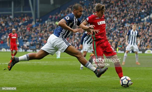 West Bromwich Albion's Venezuelan striker Salomon Rondon vies against Swansea City's English midfielder Tom Carroll during the English Premier League...