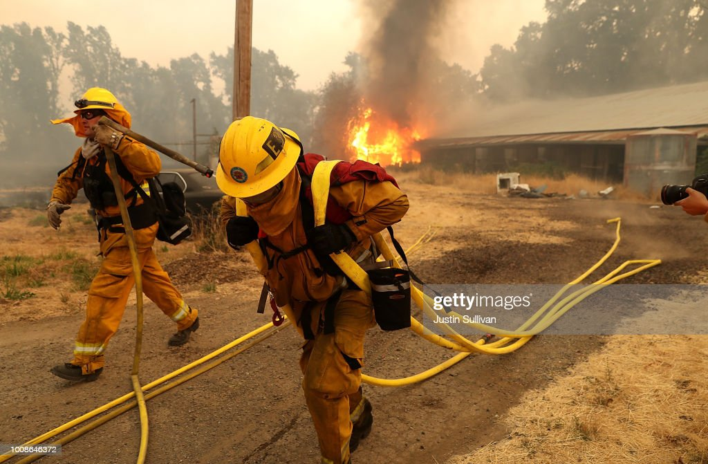 West Covina firefighters pulls hose away from a horse barn that