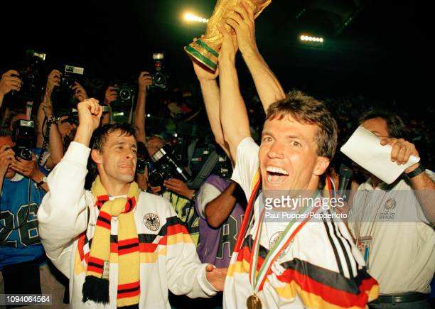 West German captain Lothar Matthaus celebrates with the trophy alongside Pierre Littbarski after the 1990 FIFA World Cup Final between West Germany...