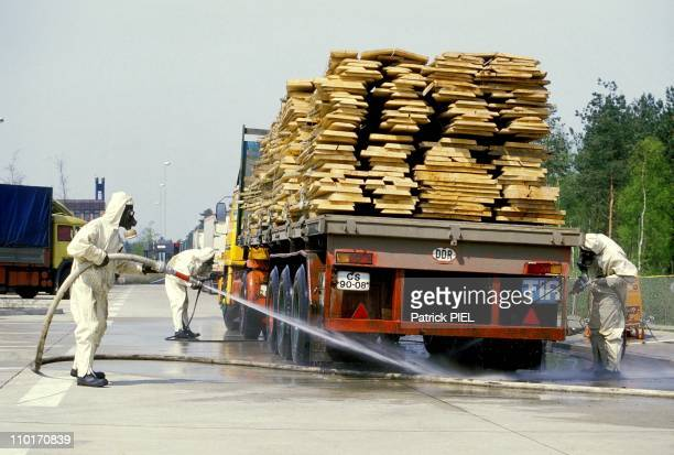 West German customs officials hose down a lorry with water they are closely screening goods, cars and people coming in from Eastern Europe, where...