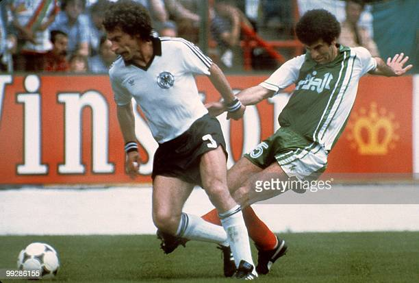 West German defender Paul Breitner tries to control the ball under pressure from Algerian midfiedler Mustapha Dahleb during the World Cup first round...