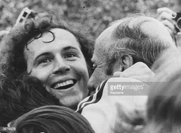 West German footballer Franz Beckenbauer beams with joy as he is embraced by coach Helmut Schon after his team beat Holland 21 to win the 1974 World...