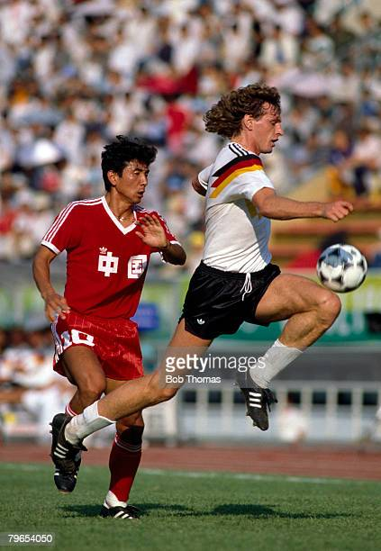 West German footballer Michael Schulz battles for the ball with China's Ma Lin during their first round Group A match of the football tournament in...