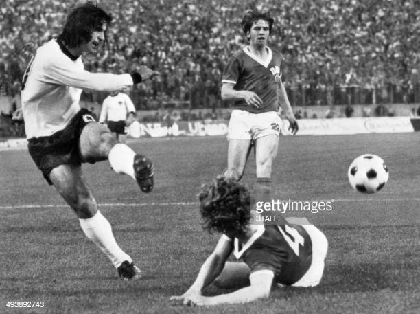 West German forward Gerd Müller kicks the ball past East German defender Konrad Weise as forward Martin Hoffmann looks on during the World Cup first...