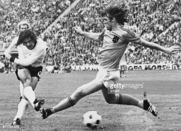 West German forward Gerd Muller scores the second goal for his team despite the being pressured by Dutch defender Rudi Krol 07 July 1974 in Munich...