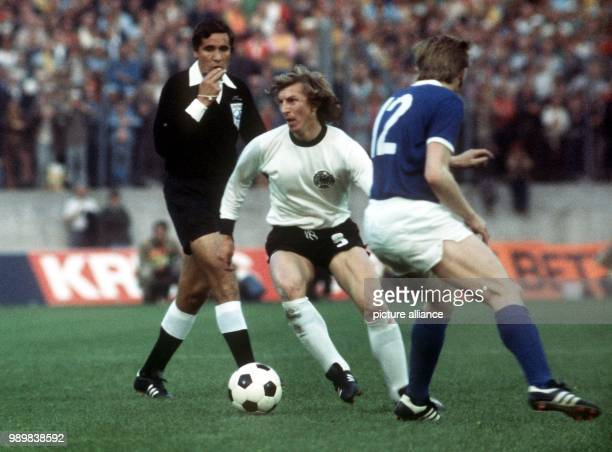 West German forward Juergen Grabowski has the ball and runs past East German defender Siegmar Waetzlich while the Uruguayan referee Ramon Barretto...