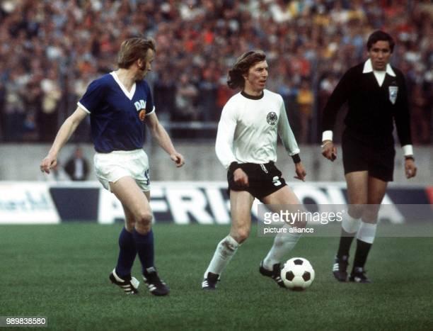 West German forward Juergen Grabowski has the ball while East German defender Siegmar Waetzlich runs next to him waiting for his chance and Uruguayan...