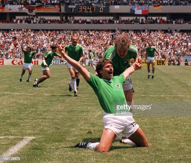 West German forward Klaus Allofs jubilates after scoring a goal against Uruguay as teammate Rudi Voller comes in to congratulate him 04 June 1986 at...