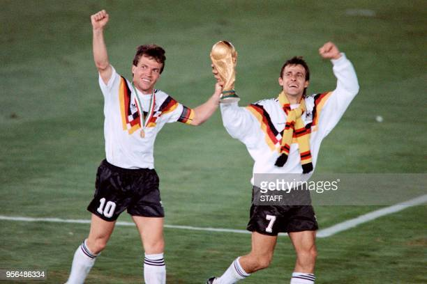 FILE West German midfielder Lothar Matthaeus and forward Pierre Littbarski celebrate with the World Cup trophy after their team beat the defending...