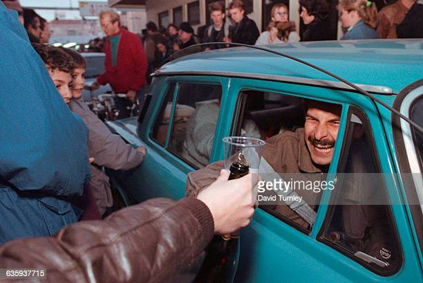 West German offers champagne to an East German passing through Checkpoint Charlie.