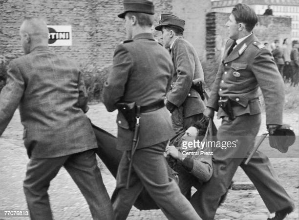 West German police arrest a young man one of the angry crowd throwing stones at a bus full of Soviet guards making their way to the Soviet War...