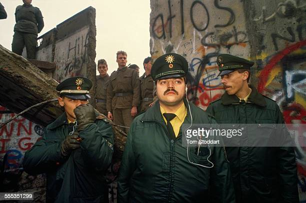 West German police guard the first section of the Berlin Wall to fall torn down by jubilant crowds near the Brandenburg Gate In the background East...