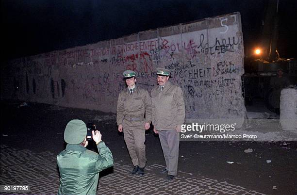West German policeman takes a photo of two east German policemen in front of the Berlin Wall on the West Berlin side on February 19 in West Berlin...