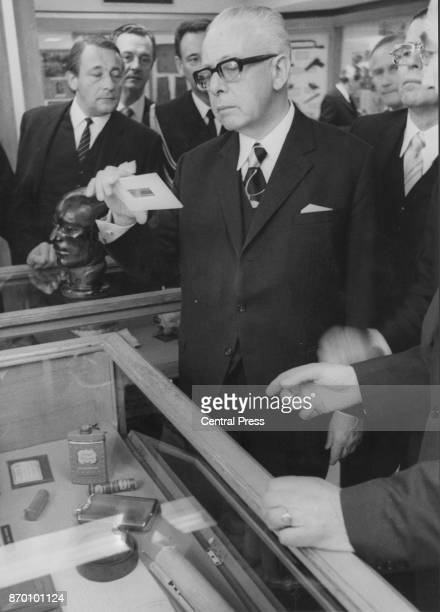 West German President Gustav Heinemann examines the microdots and talcum powder tin associated with the Lonsdale spy case during a visit to the Black...