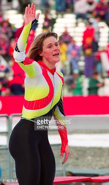 West German speed skater Gunda Niemann waves to the crowd as she catches her breath following her victory in the women's 5000m at the Winter Olympic...