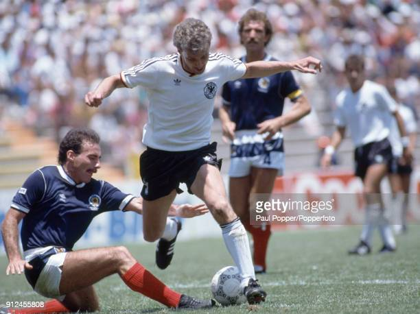 West German striker Rudi Voller is tackled by Scotland defender Willie Miller during the FIFA World Cup match between Scotland and West Germany at...