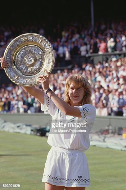 West German tennis player Steffi Graf holds the Venus Rosewater Dish trophy up in the air after winning the final of the Ladies' Singles tournament...