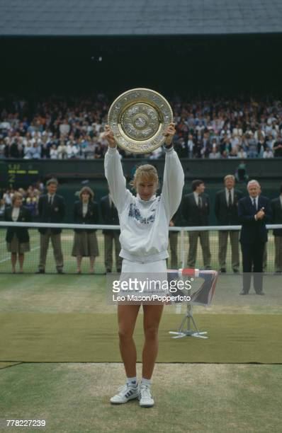 West German tennis player Steffi Graf holds the Venus Rosewater Dish trophy in the air after winning the final of the Ladies' Singles tournament...