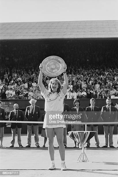 West German tennis player Steffi Graf raises the Venus Rosewater Dish trophy in the air after winning the final of the Ladies' Singles tournament...