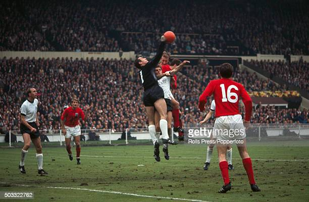 West Germany goalkeeper Hans Tilkowski punches the ball clear over the head of his teammate Wolfgang Weber whilst under pressure from Jack Charlton...