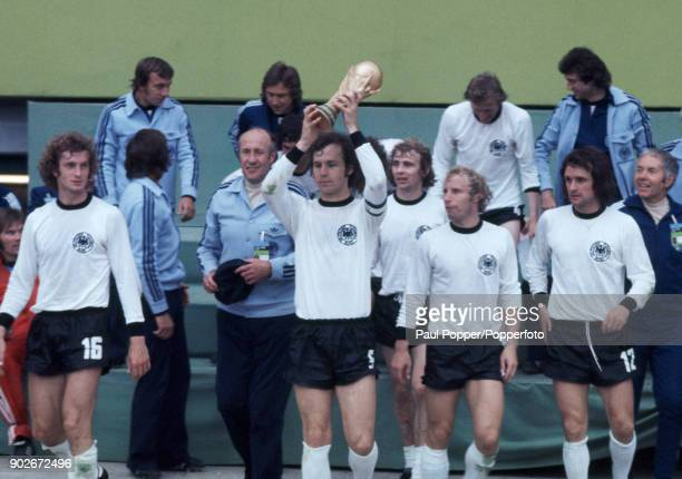 West Germany's captain Franz Beckenbauer holding the trophy as the West German team celebrate after the FIFA World Cup Final between West Germany and...