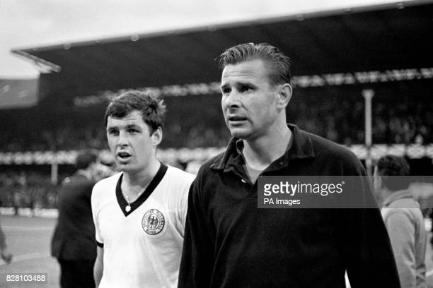West Germany's Lothar Emmerich leaves the pitch with USSR goalkeeper Lev Yashin after the match