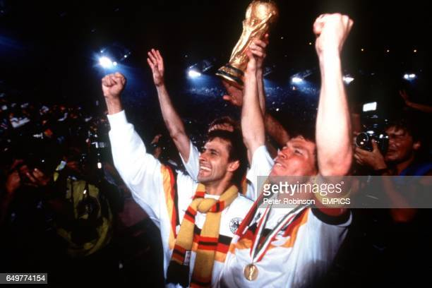 West Germany's Pierre Littbarski and captain Lothar Matthaus celebrate with the World Cup trophy