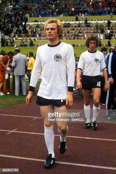 West Germany's Uli Hoeness and Bernd Hoelzenbein make their way on to the pitch