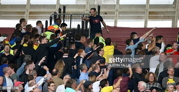 A West Ham fan top gestures towards Watford fans during the English Premier League football match between West Ham United and Watford at The London...