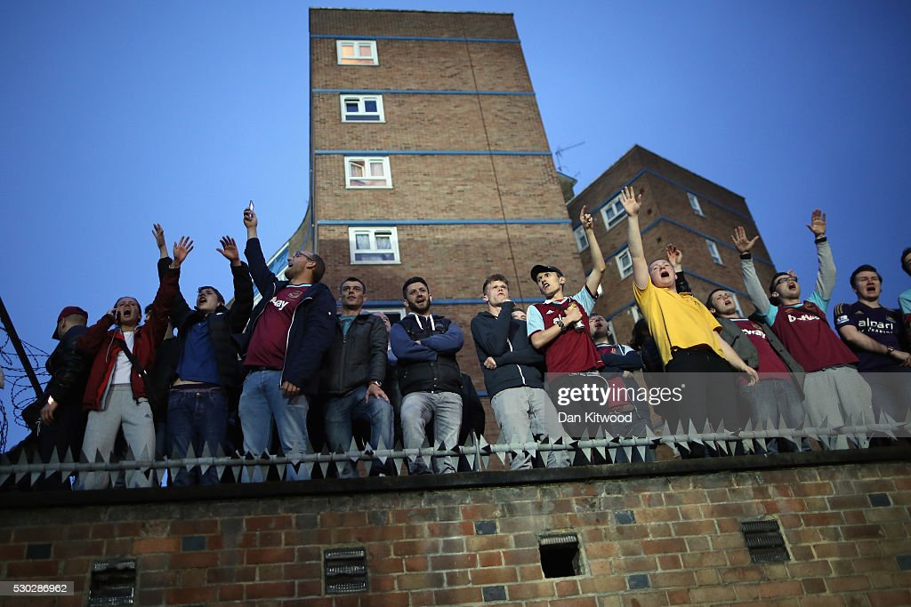 West Ham fans celebrate watch the game through a gap in the stand as they play Manchester United at the Boleyn Ground, the Home of West Ham United football club on May 10, 2016 in London, England. Tonights Premier League match against Manchester United is the last game at the Boleyn Ground, bringing to an end 112 years of the clubs history at the ground. The club will move into the Olympic Stadium next season, making way for developers and plans for 800 new homes where the stadium now stands.