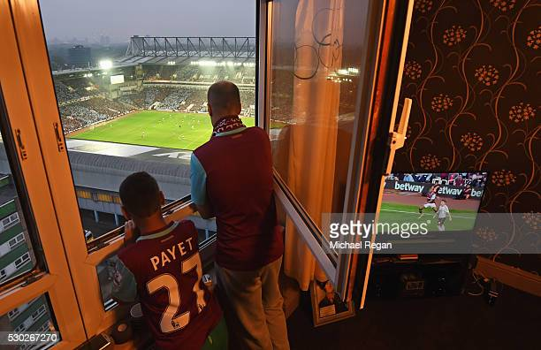 West Ham fans watch the action from a nearby block of flats during the Barclays Premier League match between West Ham United and Manchester United at...