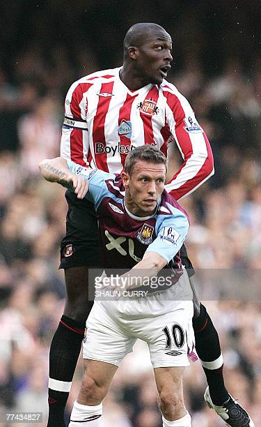 West Ham footballer Craig Bellamy tackles Sunderland's Nyron Nosworthy during their Premiership football match at the West Ham ground in East London,...