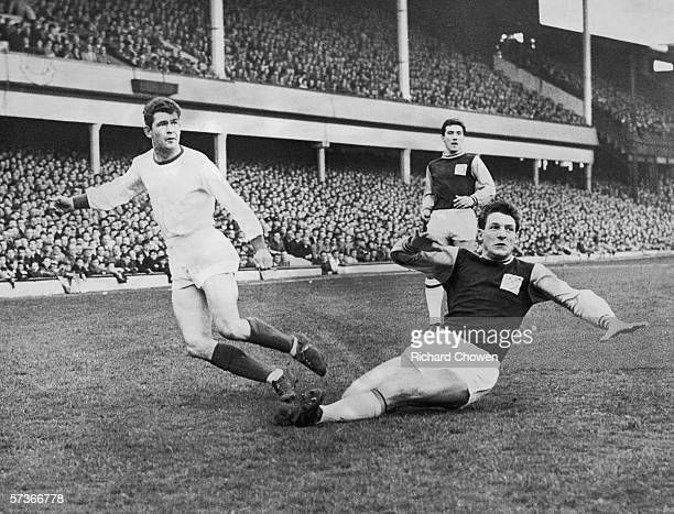 West Ham fullback John Lyall slides into the tackle at Upton Park but Arsenal winger Danny Clapton gets his centre across in the nick of time April...