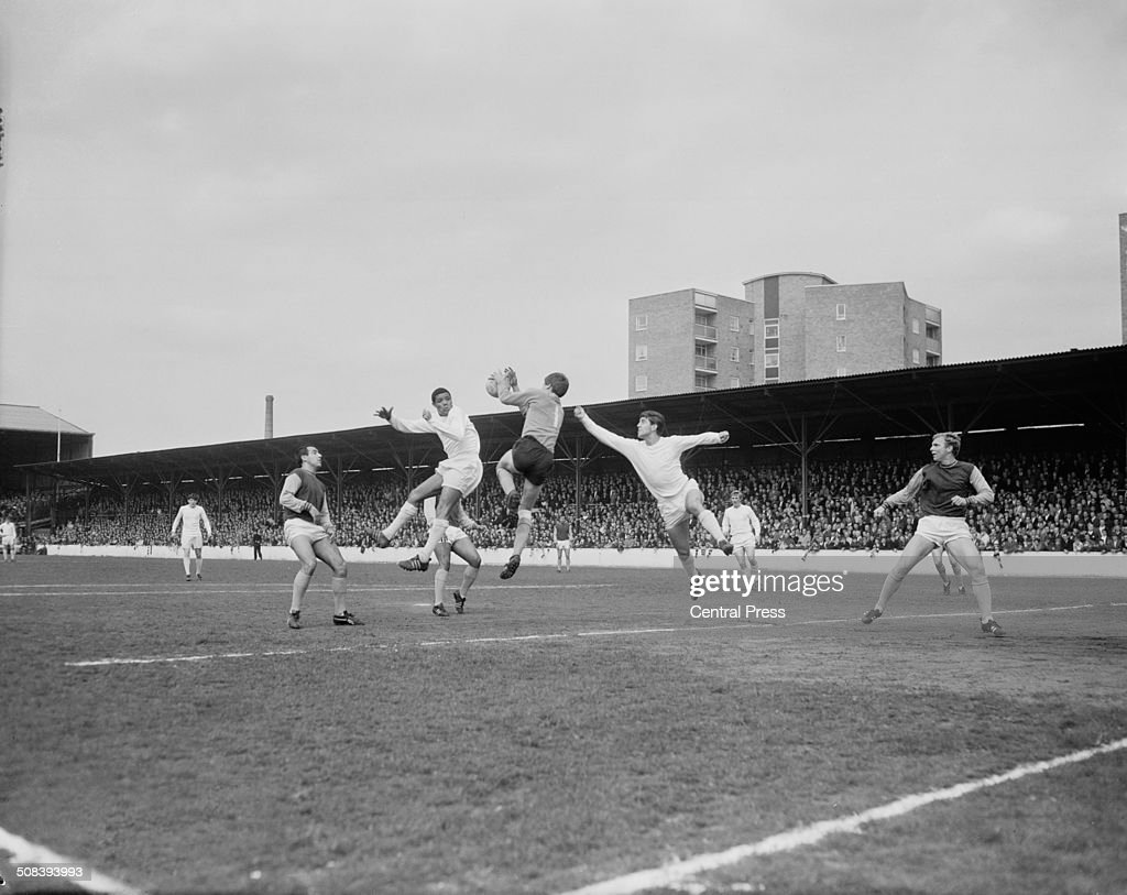 West Ham Goalkeeper Jim Standen (centre) takes the ball during an attack by Leeds United during an English Division One match at the Boleyn Ground, Upton Park, London, 22nd April 1967. In the air on either side of the keeper are Leeds players Albert Johanneson (1940 - 1995, left) and Rod Belfitt. On the far right is West Ham defender Bobby Moore (1941 - 1993). Leeds won the match 1-0.