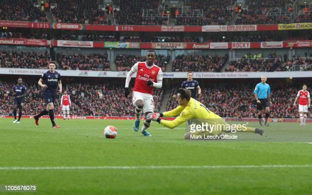 West Ham goalkeeper Lukasz Fabianski dives on the ball as Eddie Nketiah of Arsenal approaches during the Premier League match between Arsenal FC and...