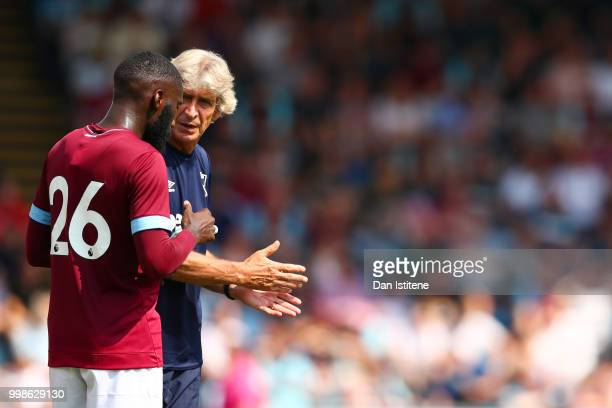 West Ham manager Manuel Pellegrini speaks with Arthur Masuaku during the preseason friendly match between Wycombe Wanderers and West Ham United at...