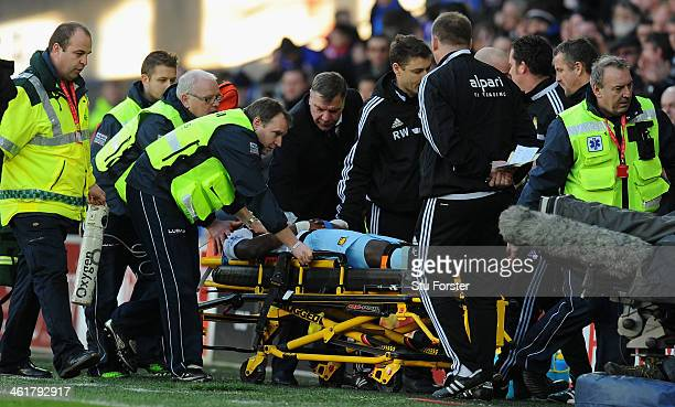West Ham manager Sam Allardyce checks on the wellbeing of player Guy Demel who is stretchered off during the Barclays Premier League match between...
