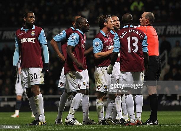 West Ham player argue with referee Mike Dean after he showed a yellow card to Luis Boa Morte of West Ham leading to a goal from a penalty to West...