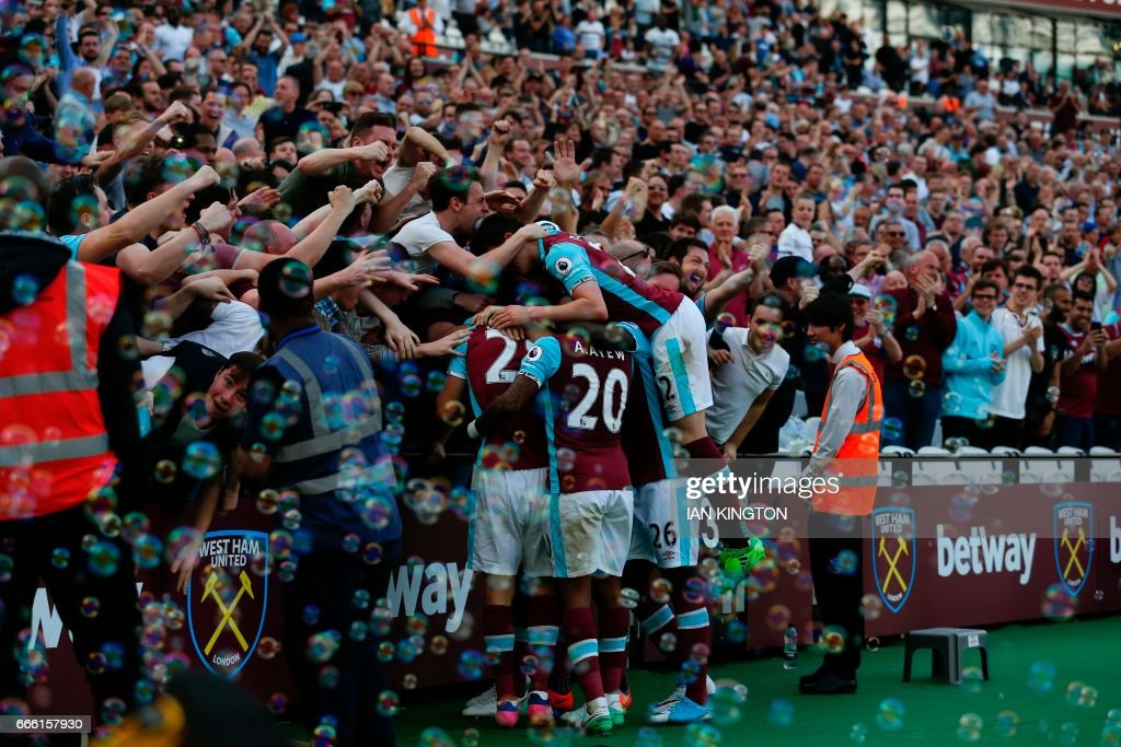 West Ham players and fans celebrate the opening goal scored by West Ham United's Senegalese midfielder Cheikhou Kouyate during the English Premier League football match between West Ham United and Swansea City at The London Stadium, in east London on April 8, 2017. / AFP PHOTO / Ian KINGTON / RESTRICTED TO EDITORIAL USE. No use with unauthorized audio, video, data, fixture lists, club/league logos or 'live' services. Online in-match use limited to 75 images, no video emulation. No use in betting, games or single club/league/player publications. /