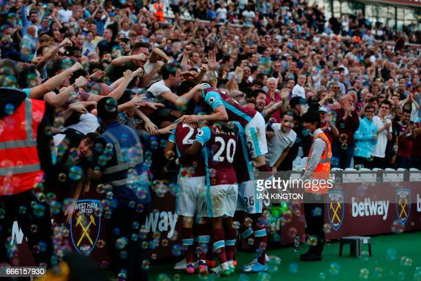 West Ham players and fans celebrate the opening goal scored by West Ham United's Senegalese midfielder Cheikhou Kouyate during the English Premier...