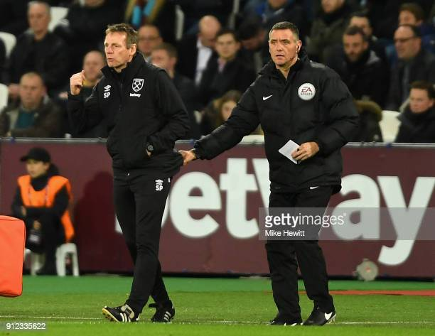 West Ham United assistant manager Stuart Pearce is pulled back into his technical area buy the fourth official during the Premier League match...