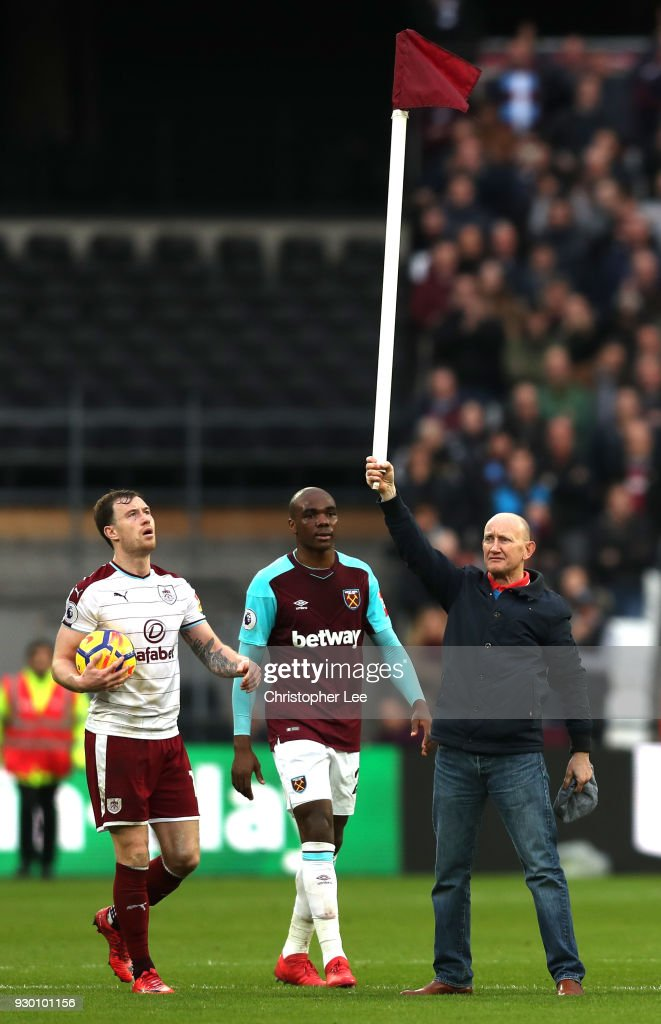 A West Ham United fan holds up the corner flag while he invades the pitch as Ashley Barnes of Burnley reacts during the Premier League match between West Ham United and Burnley at London Stadium on March 10, 2018 in London, England.