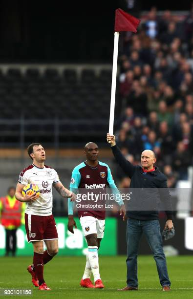 West Ham United fan holds up the corner flag while he invades the pitch as Ashley Barnes of Burnley reacts during the Premier League match between...