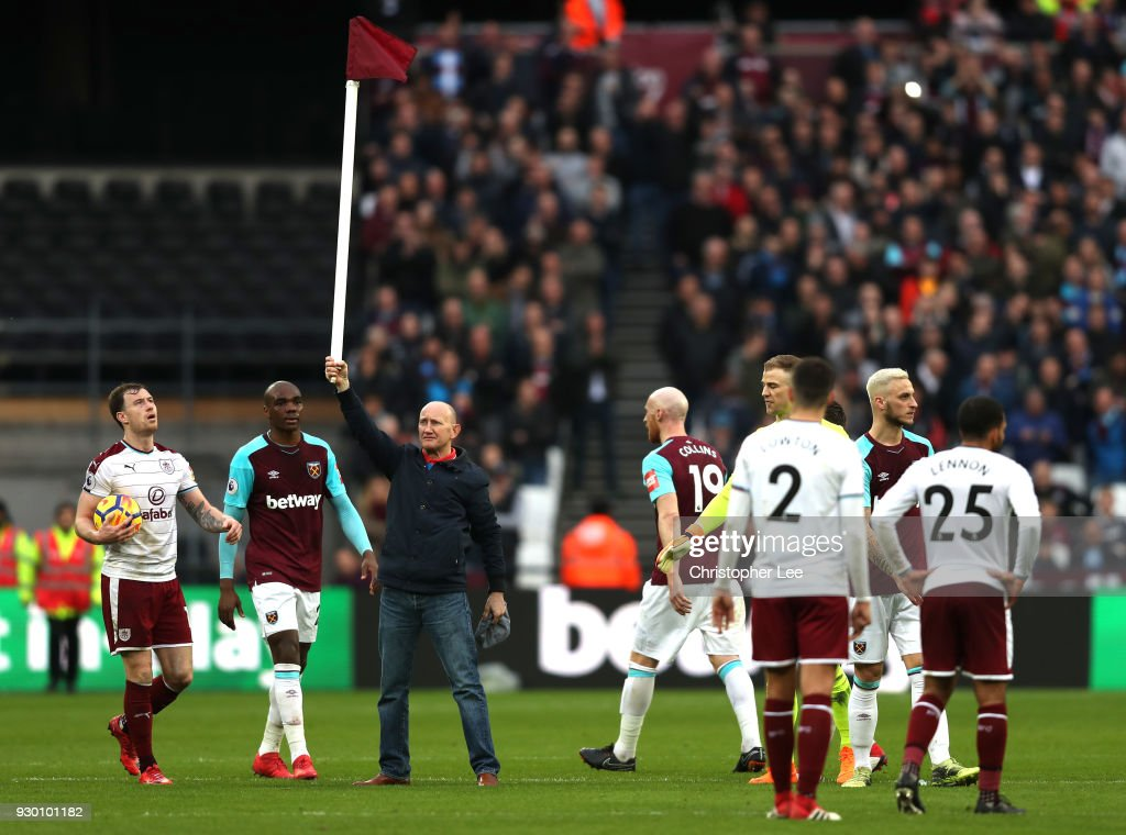 A West Ham United fan holds up the corner flag while he invades the pitch as the players react during the Premier League match between West Ham United and Burnley at London Stadium on March 10, 2018 in London, England.