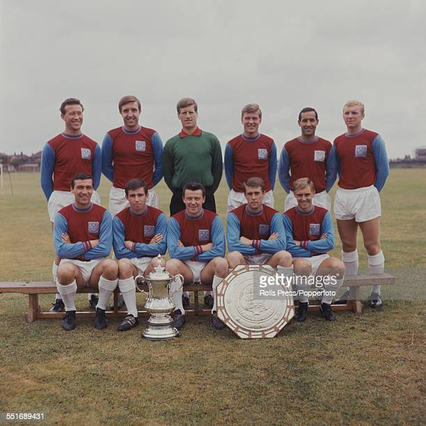 West Ham United Football squad posed during the 19641965 season with the Football Association Challenge Cup and the Football Association Charity...
