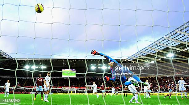 West Ham United player Andy Carroll shoots to score the opening goal past a diving Lukasz Fabianski during the Barclays Premier League match between...