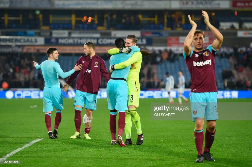 West Ham United players celebrate at the end of the English Premier League football match between Huddersfield Town and West Ham United at the John Smith's stadium in Huddersfield, northern England on January 13, 2018. / AFP PHOTO / Oli SCARFF / RESTRICTED TO EDITORIAL USE. No use with unauthorized audio, video, data, fixture lists, club/league logos or 'live' services. Online in-match use limited to 75 images, no video emulation. No use in betting, games or single club/league/player publications. /