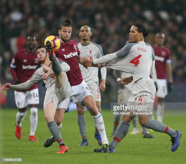 West Ham United's Andy Carroll challenges Liverpool's Virgil van Dijk and Andrew Robertson during the Premier League match between West Ham United...