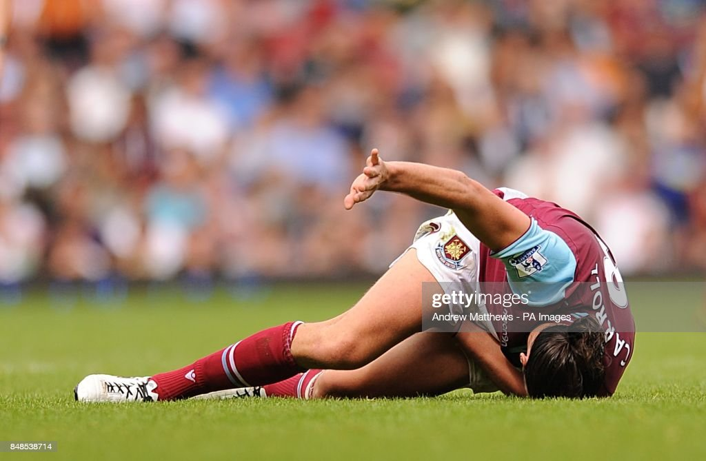 West Ham United's Andy Carroll lies in pain after picking up an injury