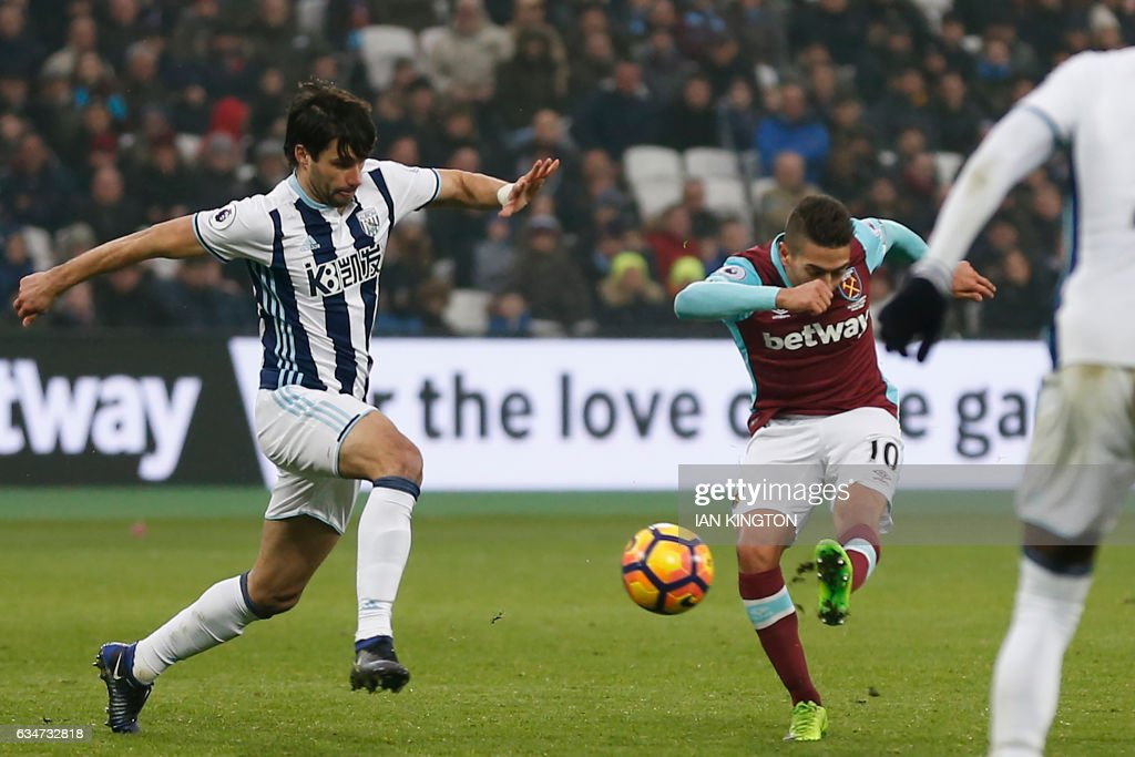 West Ham United's Argentinian midfielder Manuel Lanzini (R) shoots to score their second goal as West Bromwich Albion's Argentinian midfielder Claudio Yacob (L) closes in during the English Premier League football match between West Ham United and West Bromwich Albion at The London Stadium, in east London on February 11, 2017. / AFP / Ian KINGTON / RESTRICTED TO EDITORIAL USE. No use with unauthorized audio, video, data, fixture lists, club/league logos or 'live' services. Online in-match use limited to 75 images, no video emulation. No use in betting, games or single club/league/player publications. /